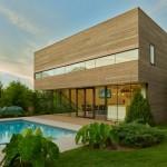 Fachada de casa revestida en madera con pileta