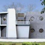 Fachada de casa con ventanas circulares y forma irregular