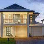 Fachada de casa iluminada con techo a 4 aguas